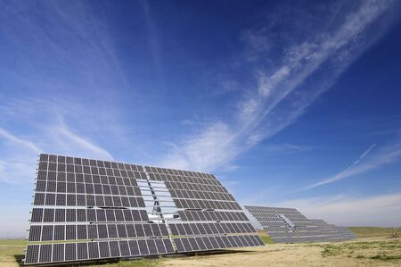 large solar panels with cloudy blue sky photo