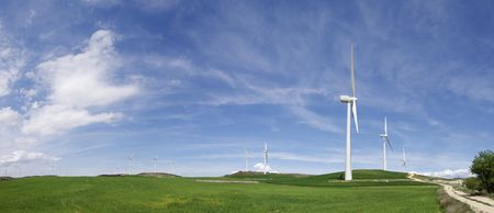 aligned windmills in green meadow with cloudy sky photo