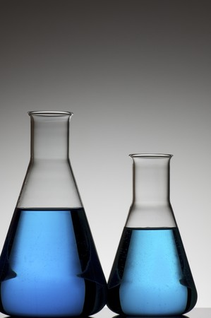 two conical flasks with liquid blue and white background Stock Photo - 6919230