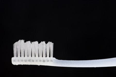 toothbrush white on black background photo