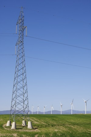 windmills aligned and high voltage electrical line with a clear blue sky photo