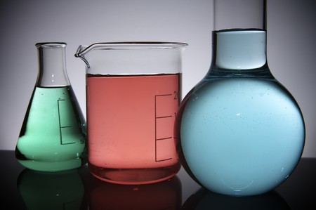 three flasks with colored liquid on a white back-light photo