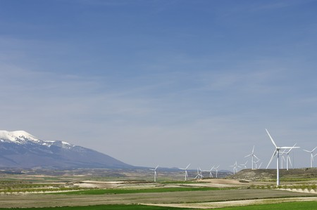 group of modern windmills and snowy mountain photo