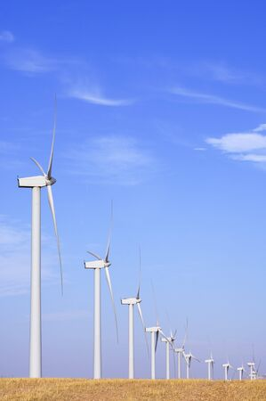 lined up: windmills lined up and blue sky with white clouds Stock Photo