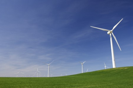 windmills on a green hill with blue sky photo