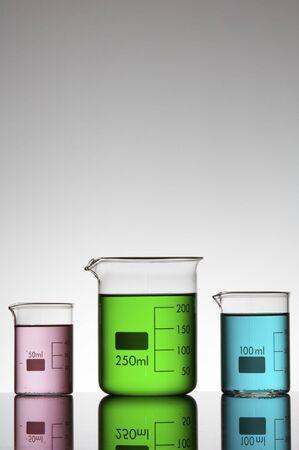 three beakers with colored liquid bright white background photo