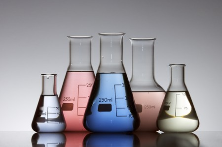 five laboratory flasks on a white backlight photo