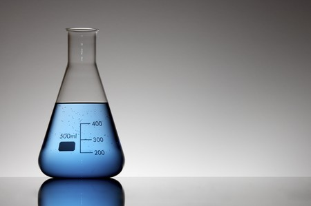 scientifical: flask with blue liquid to the light and white background Stock Photo