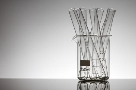 cristalería: tubos de ensayo en un vaso de precipitados con un fondo blanco  Foto de archivo