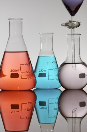 three flasks with colored liquid on a white background photo