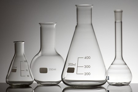 erlenmeyer: group of four empty laboratory flasks on a white background