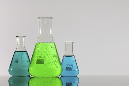 three beakers with green and blue liquid photo
