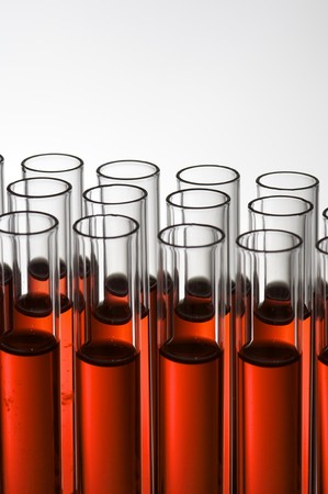 group of laboratory test tubes with red liquid inside photo