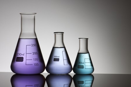 group of three conical flasks containing liquid shiny photo