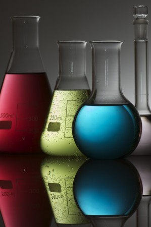 forefront of a group of flasks with brightly colored liquid photo
