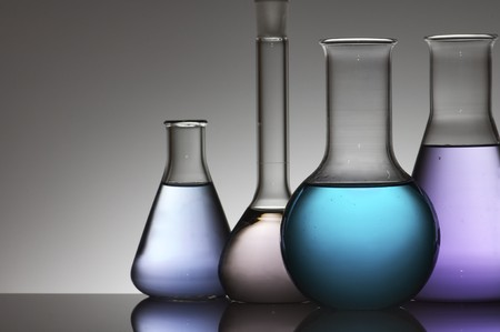 four chemical laboratory flasks with colored liquid photo
