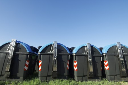 recycling bins for paper and glass with blue sky photo