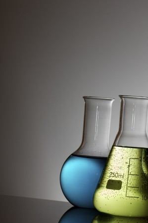 forefront of flasks with brightly colored liquid photo