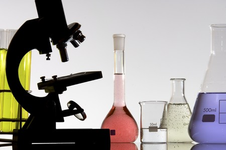 research microscope and laboratory bottles with colored liquid photo