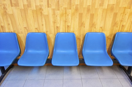 sameness: View of a group of blue plastic chairs lined