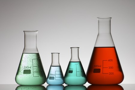 backlit: four conical glass flasks in a chemistry lab