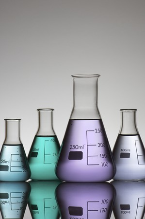 scientifical: four conical glass flasks in a chemistry lab