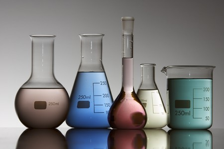 five chemical laboratory flasks containing liquid shiny color photo