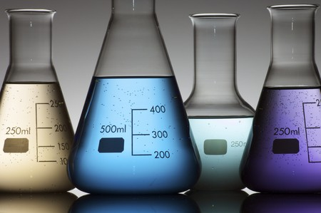 scientifical: forefront of a chemical laboratory flasks containing liquid shiny Stock Photo
