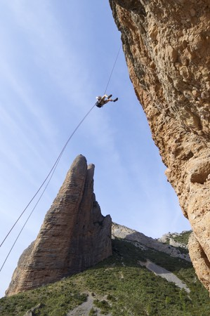 rappelling: climber descending with the technique of rappelling in Riglos mountains Stock Photo