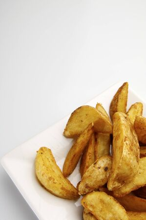 forefront: forefront of a fried potato slices on a white plate Stock Photo