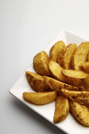 forefront of a fried potato slices on a white plate photo