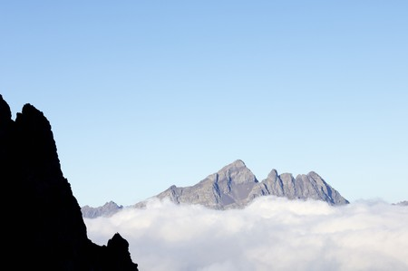looming: view of rocky mountains looming in a great sea of clouds, Pyrenees, Spain Stock Photo