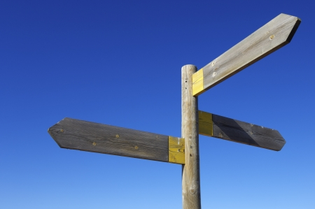 crossroad guide: view of three wooden directional signs on a pole