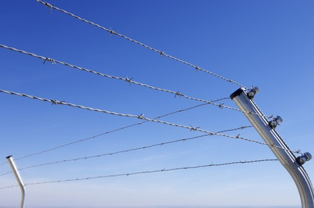foreground of a barbed wire fence on a clear day Stock Photo - 8107724