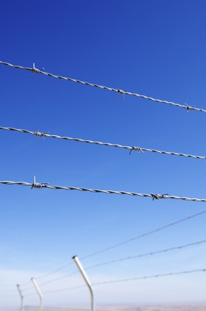 keepout: foreground of a barbed wire fence on a clear day