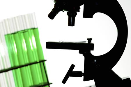 silhouette of a research microscope and test tubes with green fluid Stock Photo - 8159787