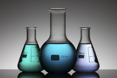 three flasks with colored liquid and a white background photo