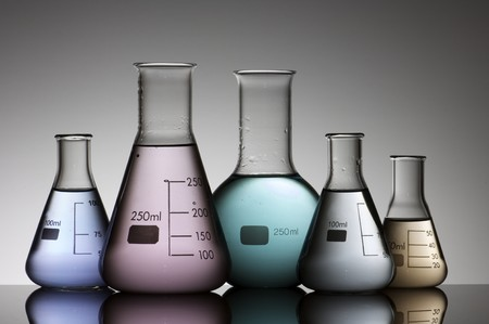 five flasks with colored liquid and a white background photo