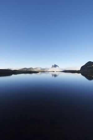 Midi Dossau peak view over a lake in the Pyrenees photo
