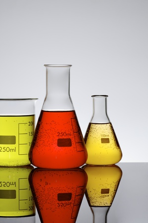 three chemical beakers with colored liquid and a white background photo