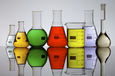 forefront of a laboratory flasks filled with colored liquid photo