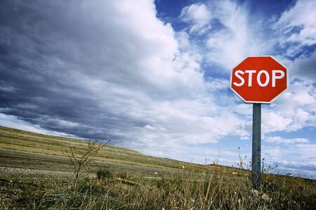 with stop sign: view of a stop signal with cloudy sky
