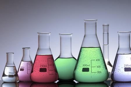 group of laboratory flasks with colored liquid inside photo