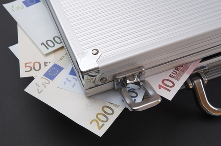 Euro banknotes  protruding from a metal briefcase photo