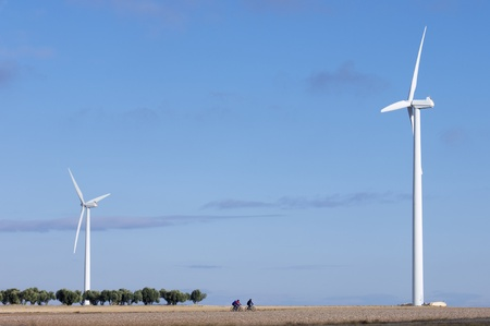 windmills for electric power generation alternative and group of cyclists photo