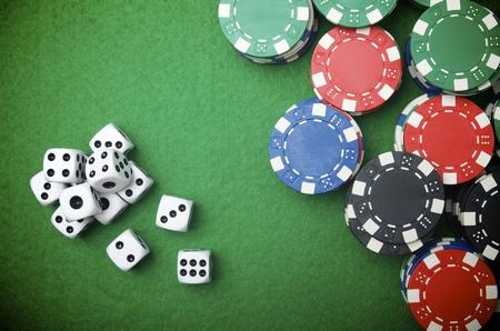fichas de casino: fichas de casino y los dados de apilamiento en un fieltro verde