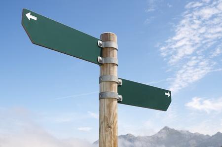 기둥에 두 나무 방향 표지판의보기
