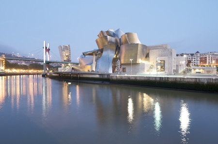 Bilbao, Biscay, Basque Country, Spain, July 30, 2011: night view of the  Guggenheim Museum and Nervion river at sunset. Guggenheim Museum is dedicated  exhibition of modern art and was  designed by architect Frank Gehry.