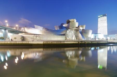 krajina: Bilbao, Biskajský záliv, Baskicko, Španělsko 30. července 2011: Noční pohled na Guggenheimova muzea, věže Iberdrola a při západu slunce. Guggenheimovo muzeum je věnováno expozici moderního umění a je dílem architekta Franka Gehryho.