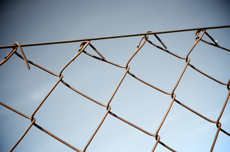 Close up of a rusty metal fence with a blue background Stock Photo - 11228125